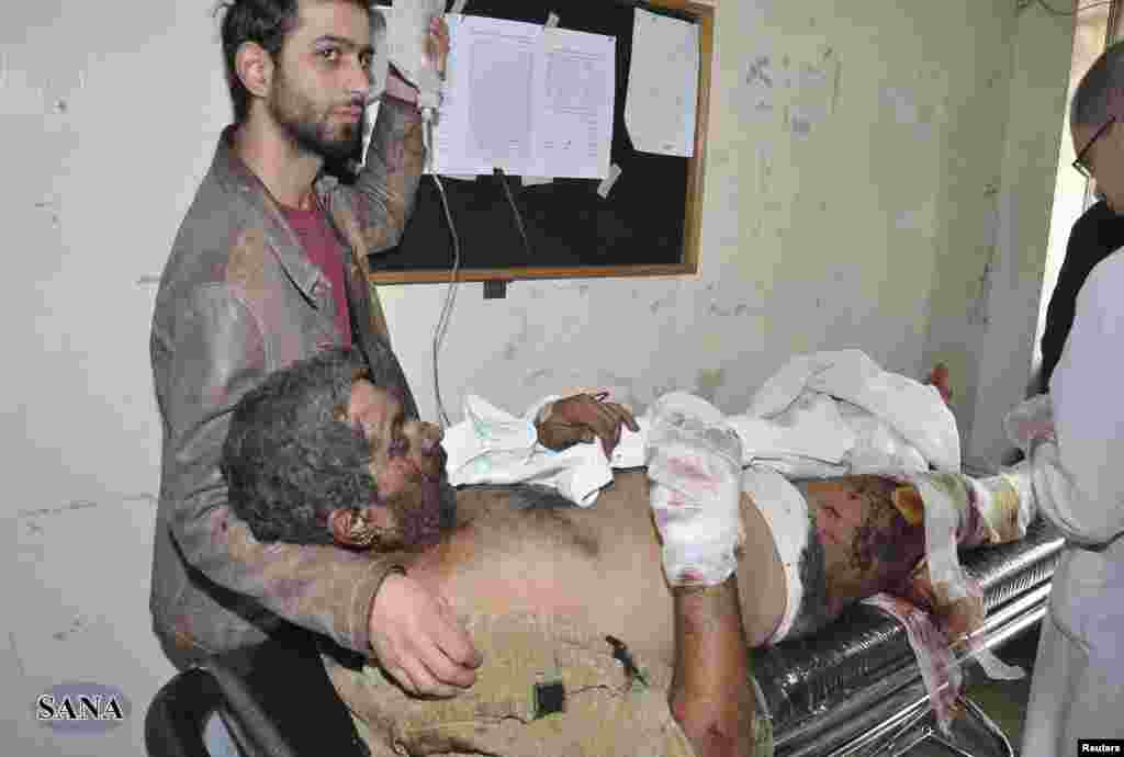 A man wounded in the explosions in Jaramana district, near Damascus, receives treatment at a hospital, in this handout photograph released by Syria's national news agency SANA, November 28, 2012.