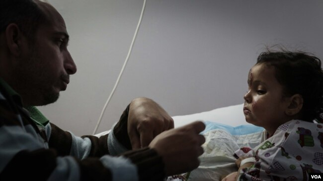 Mishaan al Abed feeds his three-year-old daughter Sarah. Sarah was among the survivors of a snowstorm that killed 16 Syrians crossing into Lebanon earlier this month.(Photo: John Owens for VOA)