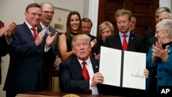 President Donald Trump shows an executive order on health care that he signed in the Roosevelt Room of the White House, Oct. 12, 2017, in Washington.