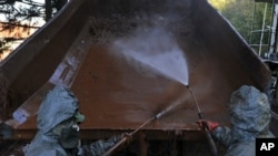 دوو سهربازی ههنگاری سهرقاڵی پاککردنهوهی گوندی کۆلۆنتارن که به قوڕ و لیته ژههراویـیهکهی عهمباره تێـکشـکاوهکه زیانی پـێـگهیشتووه، یهکشهممه 10 ی دهی 2010