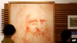 Visitors look at a portrait drawing of Italian Renaissance painter, scientist and inventor Leonardo Da Vinci in Rome, May 2, 2019. Leonardo died 500 years ago in Amboise, France, on May 2, 1519. (AP Photo/Alessandra Tarantino)