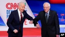 Bivši potpredsednik SAD Džozef Bajden i senator iz Vermonta Berni Sanders pozdravljaju se laktovima pred početak debate u studiju kablovske mreže CNN u Vašingtonu u nedelju 15. marta 2020. (Foto: AP/Evan Vucci)