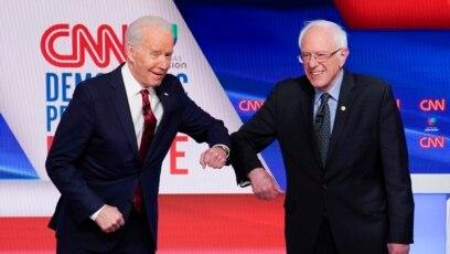 Mantan wakil presiden AS Joe Biden (kiri) dan Senator Bernie Sanders (kanan) saling menyapa sebelum debat Pilpres 2020 di Studio CNN di Washington, Minggu, 15 Maret 2020. (Foto: AP)