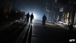 Một nhóm những người đàn ông đi bộ trên một con đường không có điện ở phía đông bắc của thủ đô Syria Damascus vào ngày 10 tháng 11 năm 2014.
