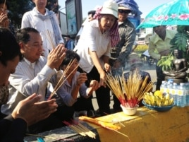 Union leader Ath Thorn (left), of the independent C.CAWDU union, joins supporters to light incense ahead of the verdict in Phnom Penh, Cambodia, May 30, 2014. (Robert Carmichael/VOA)