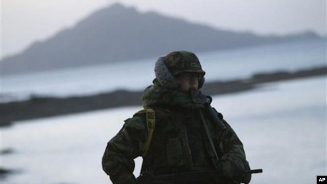A South Korean marine mans a check point along the coast of South Korea's Yeonpyeong Island Sunday, Nov. 28, 2010.