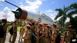 Học sinh đứng cạnh máy bay chiến đấu không còn hoạt động được trưng bày tại trường quân sự Sainik, Goalpara, bang Assam, 8/8/2014.