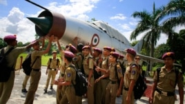 Students gather by an inactive fighter aircraft on display at a Sainik School, or military school, in Goalpara, in the northeastern Indian state of Assam, Aug. 8, 2014.