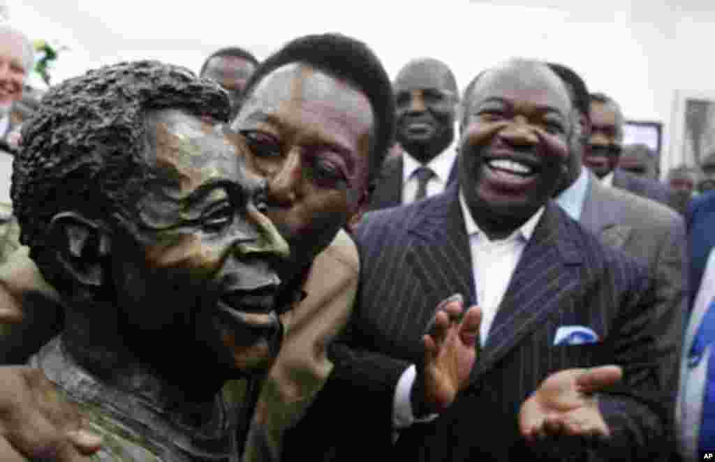 Gabon's President Ali Bongo Ondimba (R) watches as Brazil's soccer legend Pele kisses his statue during its inauguration inside the Stade De L'Amitie Stadium in Gabon's capital Libreville, February 9, 2012.