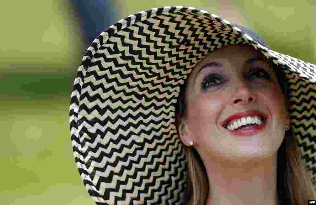 A racegoer waits for the next horse race on Ladies Day at the Epsom Derby Festival, in Surrey, southern England.