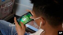 """Seorang anak memainkan game """"Honor of Kings"""" yang populer dari platform game China """"Tencent"""" dalam kereta berkecepatan tinggi dari Henan ke Beijing, 15 September 2021. China menetapkan aturan baru yang membatasi waktu yang dapat dihabiskan anak-anak untuk bermain game online.(AP)"""