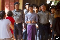 Reuters journalist Wa Lone, center, flashes thumps up as he is escorted by Myanmar police to court for trial, Feb. 1, 2018, on the outskirts of Yangon, Myanmar.