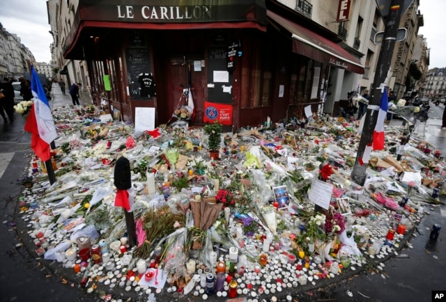 Flowers and candle tributes are placed at the Restaurant Le Carillon in Paris, Nov. 19, 2015, after the attacks.