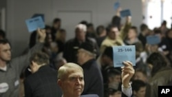 Bill Barnson, left, and others staffing precinct tables at a Washington state Republican caucus meeting, hold up signs showing precinct numbers, Saturday, March, 3, 2012, in Puyallup, Washington.