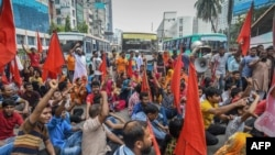 FILE - Bangladeshi garment workers and their supporters hold a rally in Dhaka, Sept. 14, 2018, to demand a higher monthly minimum wage.