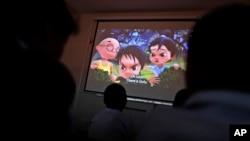 "FILE - Pakistani orphans watch an early screening of the first episode of the animated ""Burka Avenger"" series, at an orphanage on the outskirts of Islamabad, Pakistan, March 25, 2013."