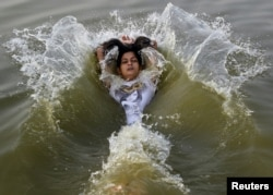 A girl cools off herself in the waters of the river Ganges during a hot summer morning in Allahabad, India, May 31, 2015.