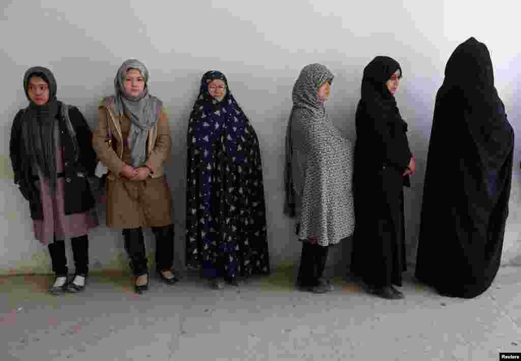 Afghan women wait in line to receive their voter registration cards in Kabul for the Afghan presidential elections scheduled for April 5.