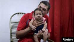 Glecion Fernando holds his 2-month-old son Guilherme Soares Amorim, who was born with microcephaly, near at her house in Ipojuca, Brazil, Feb. 1, 2016.