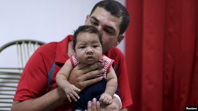 FILE - Glecion Fernando holds his 2-month-old son, Guilherme Soares Amorim, who was born with microcephaly, in Ipojuca, Brazil, Feb. 1, 2016.