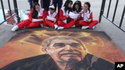 FILE - Students read guides to Bogota's International Book Fair, as they sit next to a chalk painting of the late Colombian novelist Gabriel Garcia Marquez, in Bogota, Colombia, April 28, 2015.
