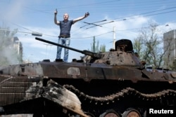 A man reacts as he stands on top of burnt-out armoured personal carrier near the city hall in Mariupol, eastern Ukraine May 10, 2014.