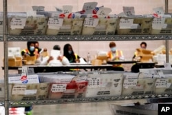Workers with the Philadelphia City Commissioners office sort election materials for the 2020 General Election in the United States at the city's mail-in ballot sorting and counting center, in Philadelphia, Oct. 26, 2020.