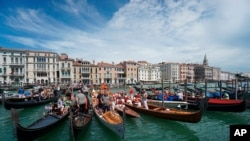 FILE - In this Sunday, June 21, 2020 file photo, gondolas are lined up during the Vogada della Rinascita (Rowing of Rebirth) regatta, along Venice canals, Italy. European Union envoys are close to finalizing a list of countries whose citizens will…