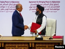FILE - Mullah Abdul Ghani Baradar and Zalmay Khalilzad, U.S. envoy for peace in Afghanistan, shake hands after signing an agreement at a ceremony in Doha, Qatar, Feb. 29, 2020.