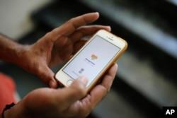 An Indian man uses Aarogya Setu app on his mobile phone in New Delhi, India, May 7, 2020.