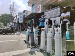 Indonesians, fortunate to have their own oxygen tanks, line up at an oxygen supply station in Tebet, Jakarta, July 4, 2021, after a hospital ran out of supplemental oxygen, asking patients' families to bring their own. (Indra Yoga/VOA-Jakarta)