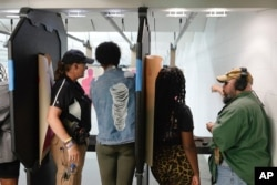 In this Aug. 21, 2021, image taken from video, firearms instructors, left, and right, teach female customers on the shooting range at the Recoil Firearms store in Taylor, Mich.