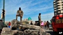 Pripadnici bezbednosnih snaga stražare na barijeri koja blokira mesto održavanja demonstracija tokom antivladinih protesta u Bagdadu, Irak, 15. februara 2020. (AP Photo/Hadi Mizban)
