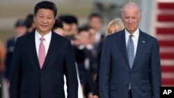 FILE - In this Sept. 24, 2015 file photo, Chinese President Xi Jinping and Vice President Joe Biden walk down the red carpet on the tarmac during an arrival ceremony in Andrews Air Force Base, Md.