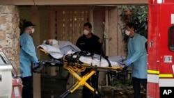 10일 미국 워싱턴주 시애틀 근교의 커클랜드 노인 요양원에서 의료관계자들이 신종 코로나바이러스 감염증(COVID-19) 환자를 구급차로 이송하고 있다.