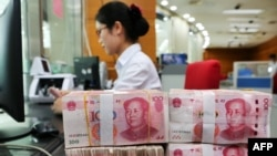 在中国江苏省南通市的一家银行,一名员工处理100元纸币。(2018年7月23日)