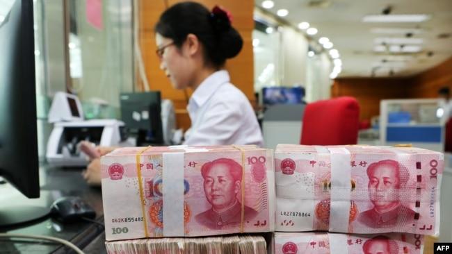 Nhân viên ngân hàng đang kiểm tra đồng 100 tệ tại một ngân hàng ở Nam Thông, Trung Quốc.
