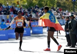 Meb Keflezighi of USA (L) gets a high five from Gebre Gebremariam of Ethiopia as Keflezighi runs for the finish line where he finished fourth in the men's professional division of the 2014 New York City Marathon in Central Park in Manhattan, Nov. 2, 2014.