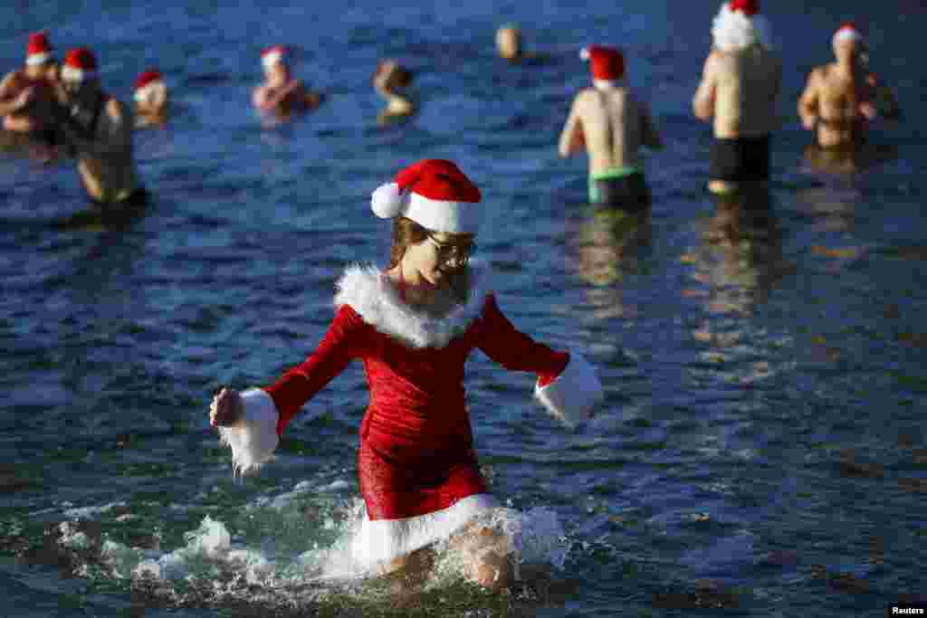 "Members of the ice swimming club ""Berliner Seehunde"" (Berlin Seals) take a dip in the Orankesee lake as part of their traditional Christmas swimming session in Berlin, Germany."