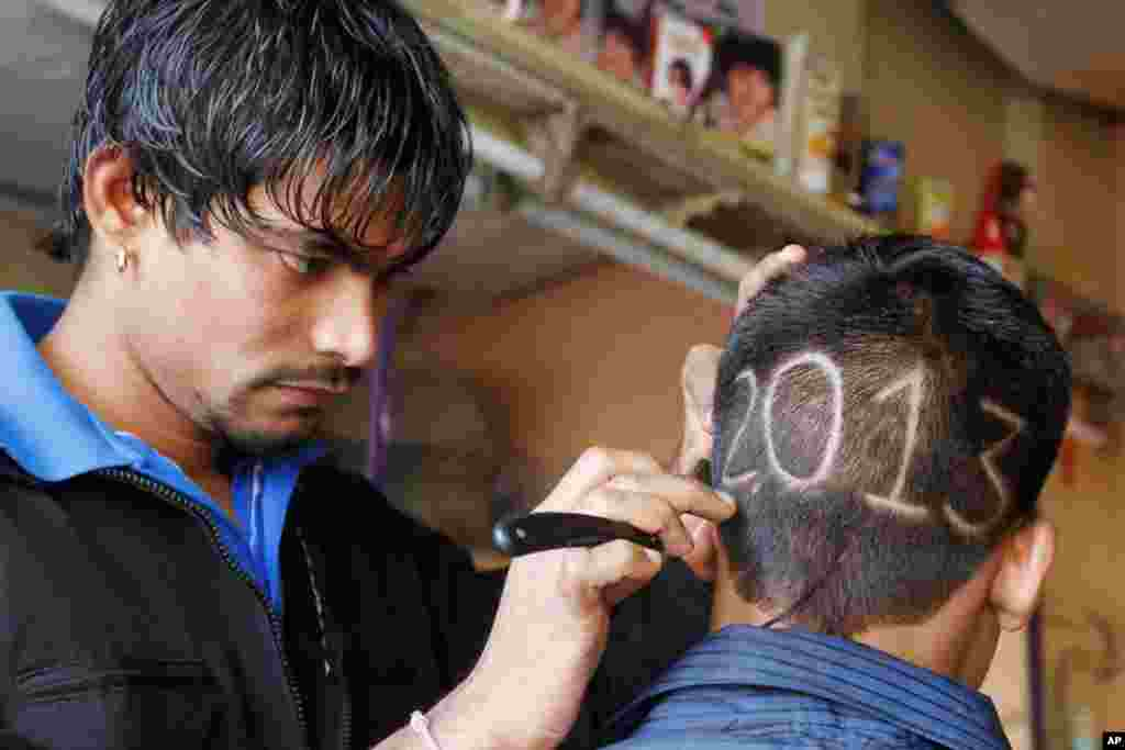 An Indian barber gives finishing touches to the hair style of a young boy with numbers to welcome the New Year 2013 in Ahmadabad, India, December 31, 2012.