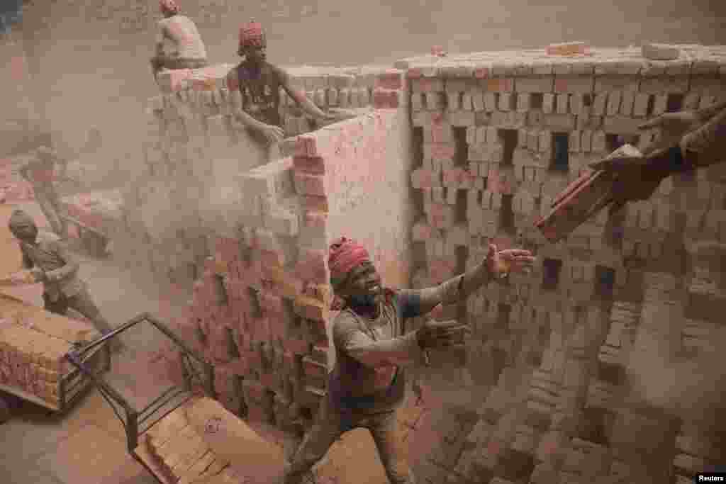Brick factory workers stack bricks on a cart to take them to the warehouse in Dhaka, Bangladesh.