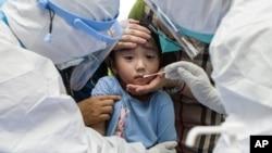 在武漢大規模檢測COVID-19 時,一名兒童對咽拭子做出反應。