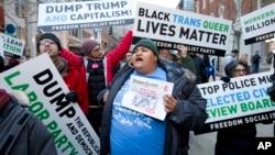 Manifestantes marchan en la calle cerca de un puesto de control de seguridad para ingresar a la ceremonia de asunción de Donald Trump en Washington.