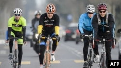 FILE - In this picture taken on March 16, 2015 US Secretary of State John Kerry (2-L) rides his bike during a break in Lausanne.