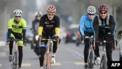 Foto bertanggal 16 Maret 2015 ini menunjukkan Menteri Luar Negeri AS John Kerry (kedua kiri) mengedarai sepedanya di sela-sela waktu luangnya di Lausanne. (Foto: dok.)