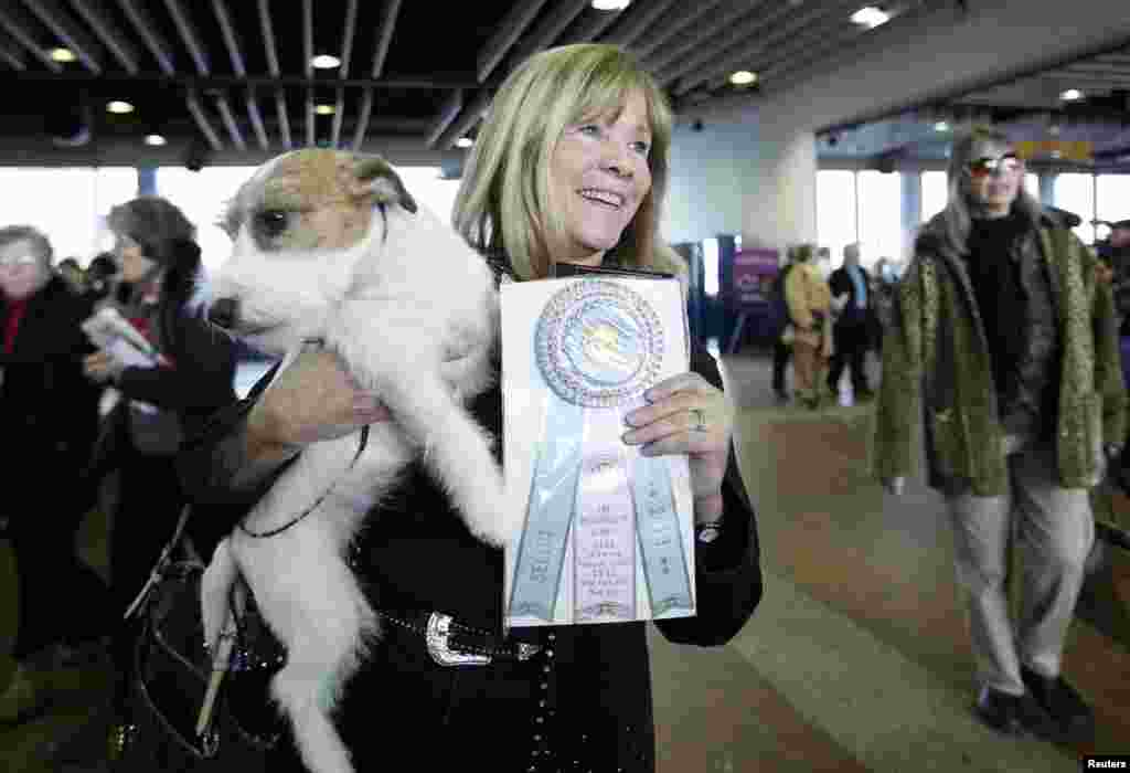 Sue Sobel holds up Maddy, a Russell terrier who won the Winners Bitch during the 137th Westminster Kennel Club Dog Show in New York, February 12, 2013.