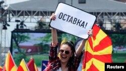 """Seorang perempuan mengibarkan poster bertuliskan """"mengundurkan diri"""" dalam demo anti pemerintah di Skopje, Macedonia, 17 Mei 2015."""