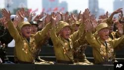 Para tentara veteran Perang Korea melambaikan tangan untuk pemimpin mereka, Kim Jong-un dalam parade militer memperingati 60 tahun berakhirnya perang Korea (27/7).