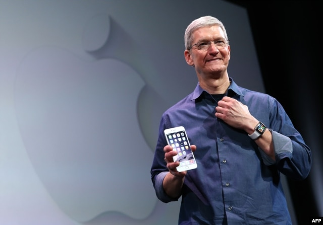 FILE - Apple CEO Tim Cook shows off the new iPhone 6 and the Apple Watch during an Apple special event at the Flint Center for the Performing Arts in Cupertino, California.