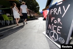 "A couple walk through the empty flower market in the old city and near a sign which reads, ""Pray for Nice"" days after a truck attack on the Promenade des Anglais on Bastille Day killed scores and injured as many in Nice, France, July 17, 2016."